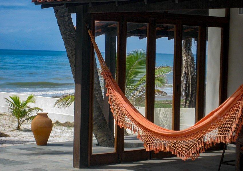 hangmat naast zwembad met zicht op tuin en zee ultieme ontspanning vakantie in Brazilië
