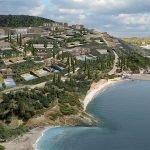 hera bay luxury resort helikopterzicht over heuvelflank en baai unieke inplanting en locatie