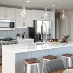 keuken met fornuis oven microgolf amerikaanse frigo en verhoogde ontbijttafel met barkrukken retro armaturen lampen