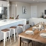woonkamer met open keuken mooie houten tafel passend bij parket en stijlvolle ingebouwde amerikaanse koelkast