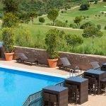 gemeenschappelijk zwembad met ligzetels bartafels en uitzichten over golfbaan en heuvels estepona málaga costa del sol