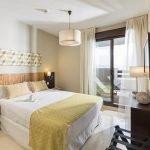 grote slaapkamer met luxe tweepersoonsbed tv aan de muur en kwaliteitsvol meubilair in appartement te koop aan de costa del sol spanje