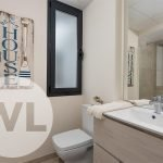 lavabo met opbergruimte en inloopdouche met regendouche en toilet in de hoek