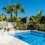 ruim privé terras met ligzetels aan privé zwembad en privé tuin met mooi bananen en palmbomen spanje santiago de la ribera