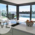 zicht vanuit open keuken op terras zwembad en tuin luxe nieuwbouw huis te koop spanje santiago de la ribera