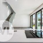 zicht vanuit keuken met kookeiland op woonkamer trap naar bovenverdieping en tuin met privé zwembad spanje nieuwbouw villa te koop