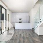 zicht vanuit woonkamer op open keuken en trap naar bovenverdieping spaanse villa te koop aan costa cálida