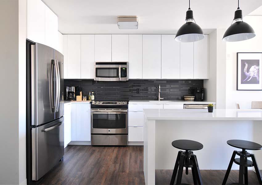 keuken met kookfornuis frigo verhoogde eettafel en barstoelen pluspunt voor huurders