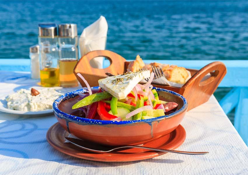 verse griekse salade met brood en olijfolie tafelen op samos met egeïsche zee op achtergrond